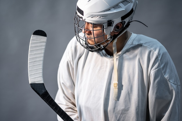 Jogador de hóquei no gelo profissional sentir-se irritado, uma iluminação no quarto escuro. Foto Premium