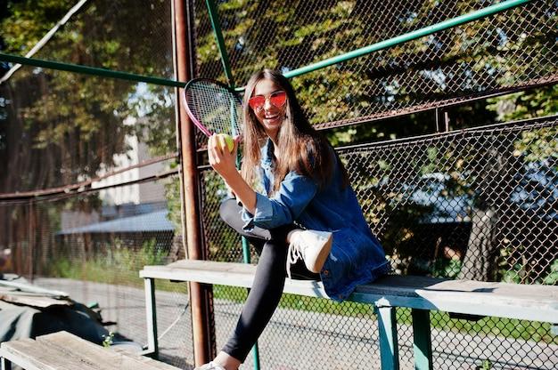 Jogador desportivo novo com a raquete de tênis no campo de tênis. Foto Premium