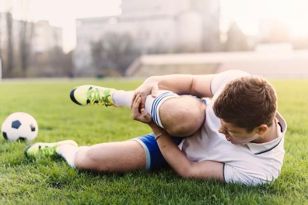 Jogador futebol, segurando, ferido, perna Foto gratuita