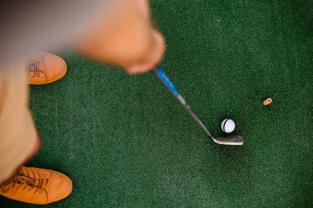 Jogador leigo plana segurando um clube Foto gratuita