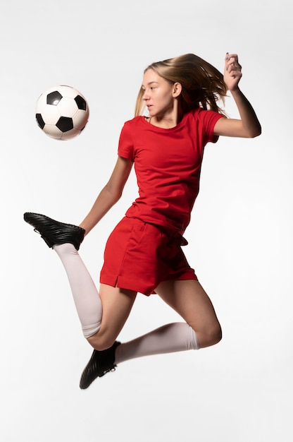 Jogadora de futebol chutando bola Foto gratuita