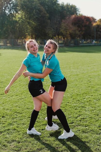Jogadores de futebol feminino, abraçando uns aos outros Foto gratuita