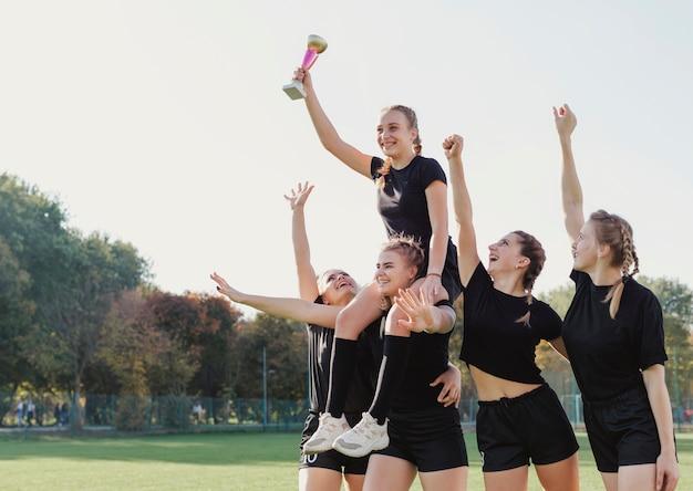 Jogadores de futebol feminino, ganhando um troféu Foto gratuita