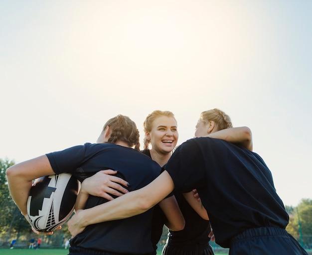 Jogadores de rugby femininos, abraçando uns aos outros Foto gratuita