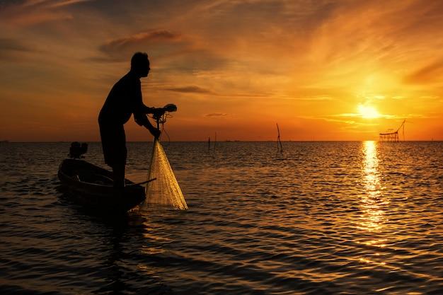 Jogando a rede de pesca durante o nascer do sol, tailândia Foto Premium