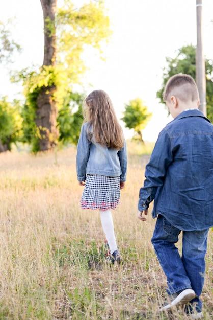 Jogando as crianças no campo verde durante o dia quente de verão Foto Premium