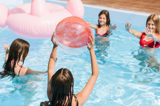 Jogando o tempo na piscina com uma bola de praia Foto Premium