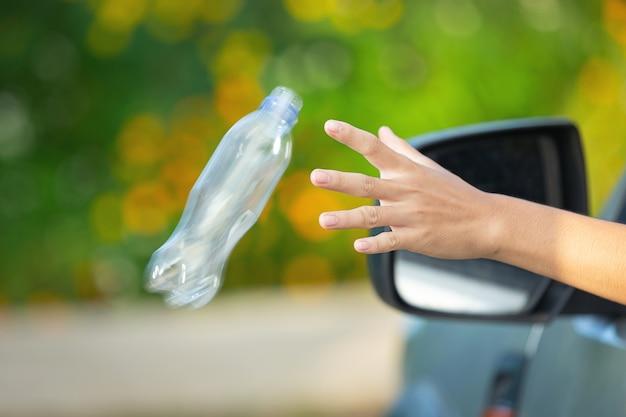 Jogando uma garrafa de plástico pela janela do carro Foto gratuita