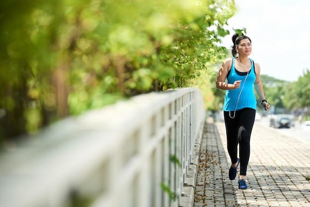 Jogging garota correndo ao ar livre com fones de ouvido, ouvindo música Foto gratuita
