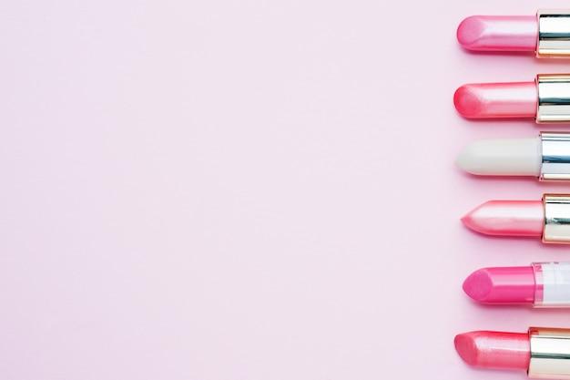 Jogo de batons cor-de-rosa coloridos no fundo cor-de-rosa. cosméticos femininos. foco seletivo. copie o espaço. Foto Premium