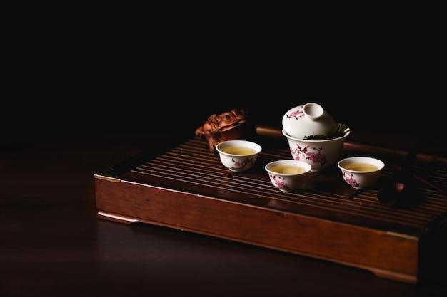 Jogo de chá chinês na mesa de chá chaban no fundo preto. cerimônia do chá chinês. Foto gratuita
