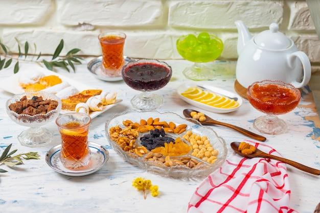 Jogo de chá com variedades de nozes tradicionais, limão, confiture e doces servidos na toalha de mesa branca Foto gratuita