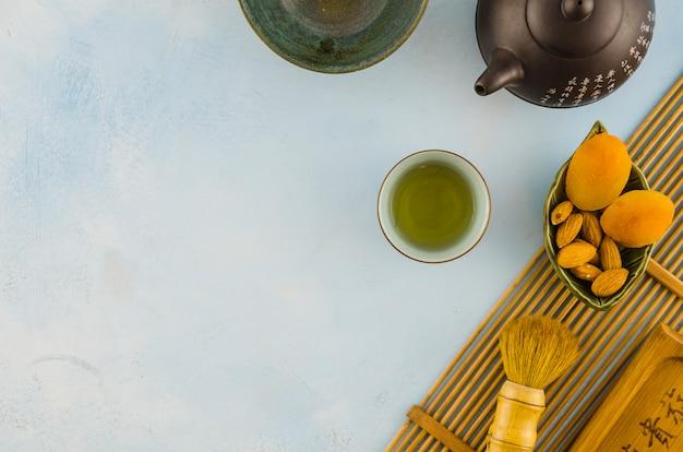 Jogo de chá oriental com escova e frutas secas no pano de fundo branco Foto gratuita