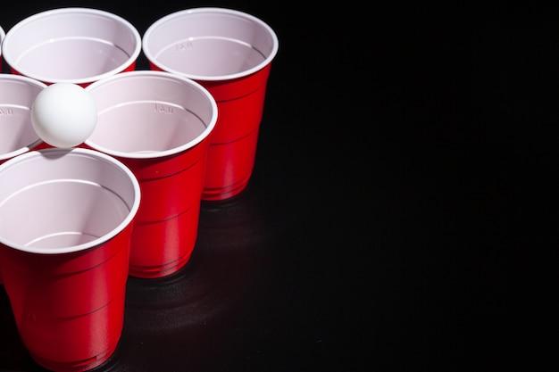 Jogo de faculdade de cerveja pong em fundo preto Foto Premium
