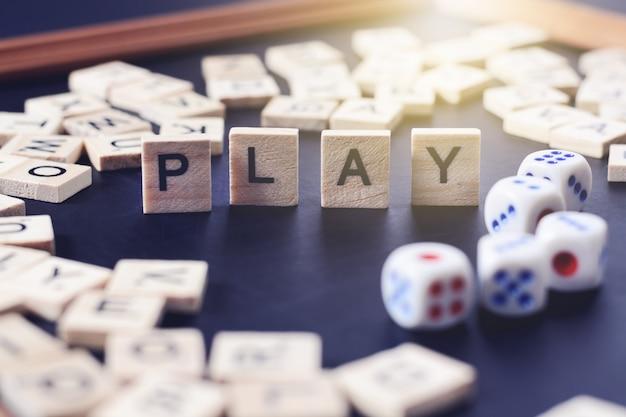 Jogo de palavras com letras de madeira no quadro negro com dados e carta no círculo Foto Premium