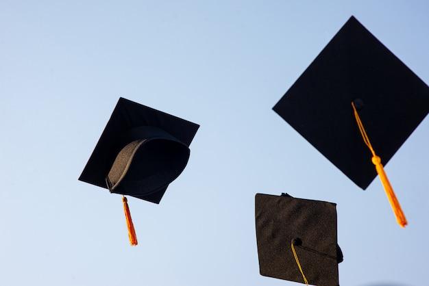 Jogue um chapéu preto de graduados no céu. Foto Premium