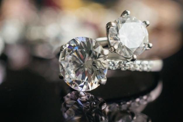Joias com anéis de diamante na superfície preta com reflexo Foto Premium