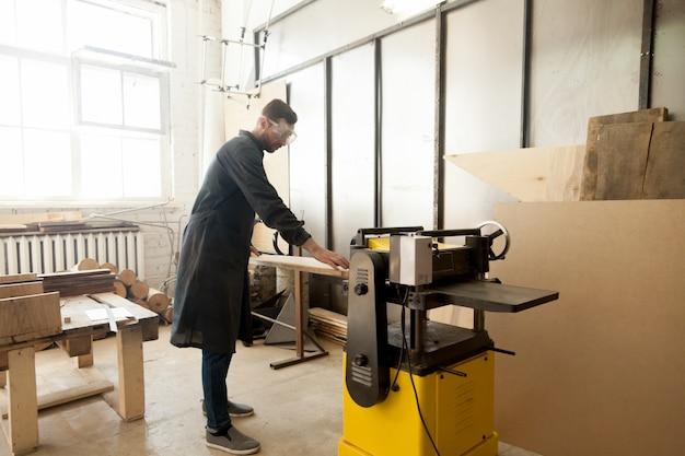 Jointer em vestuário de proteção de processamento de madeira na ferramenta elétrica estacionária Foto gratuita