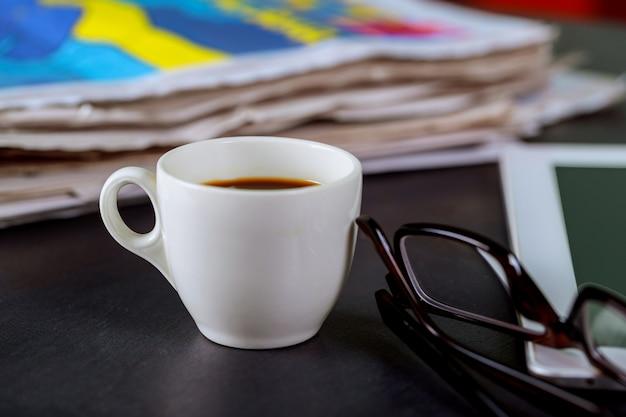 Jornais e xícara de café, óculos de leitura e bloco de notas Foto Premium