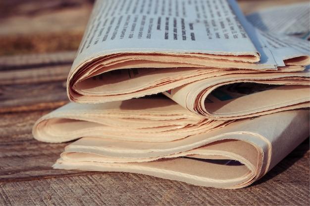 Jornais em fundo de madeira velho. Foto Premium