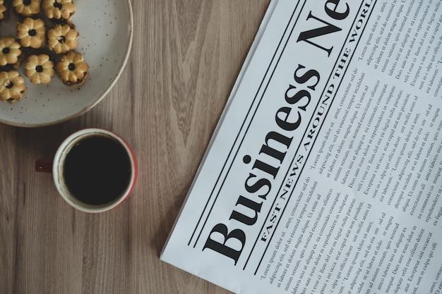 Jornal, uma xícara de café e lanches em uma mesa de madeira. Foto Premium