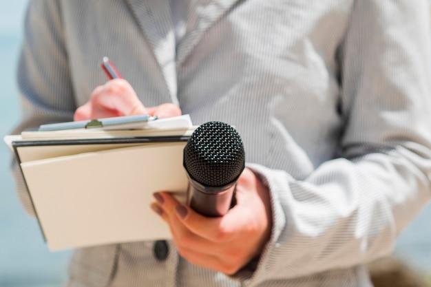 Jornalista de close-up, escrevendo no caderno Foto Premium