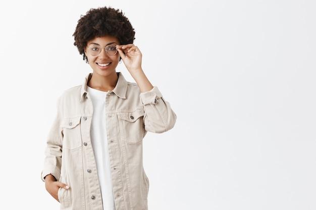 Jornalista inteligente e criativa de camisa bege e óculos, tocando a borda dos óculos, sorrindo, segurando a mão no bolso, autoconfiante e satisfeita com ótimo resultado Foto gratuita