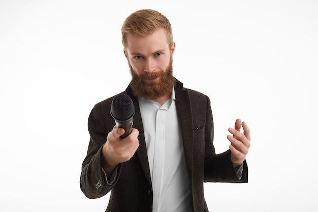 Jornalista masculino barbudo elegante vestido com uma jaqueta elegante apontando o microfone na frente durante a entrevista, tendo olhar desconfiado. Foto gratuita