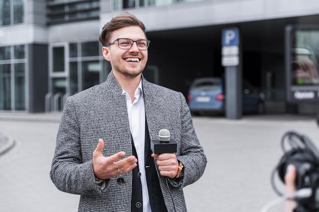 Jornalista sorridente no trabalho Foto gratuita