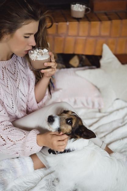 Jovem à beira da lareira beber cacau com marshmello com cachorro. Foto gratuita