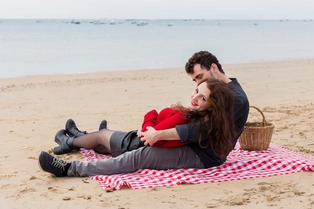 Jovem, abraçando, mulher, sentando, ligado, coverlet Foto gratuita