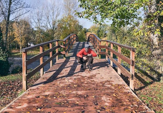 Jovem, abraçando seu cachorro no final de uma ponte de madeira em uma manhã fria de outono. Foto Premium