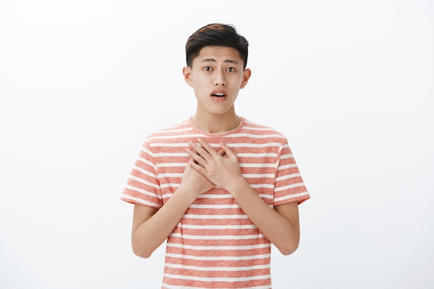 Jovem adolescente asiático emocionado e deliciado erguendo as sobrancelhas Foto gratuita