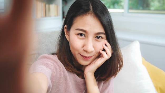 Jovem adolescente asiático mulher vlog em casa, feminino usando smartphone fazendo vídeo vlog para mídias sociais na sala de estar. a mulher do estilo de vida relaxa no conceito da manhã em casa. Foto gratuita