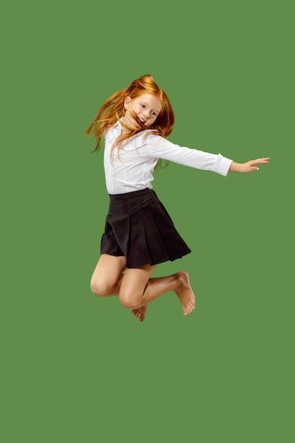 Jovem adolescente caucasiana feliz pulando no ar, isolado no fundo verde do estúdio. belo retrato feminino de meio corpo. emoções humanas, conceito de expressão facial. Foto gratuita