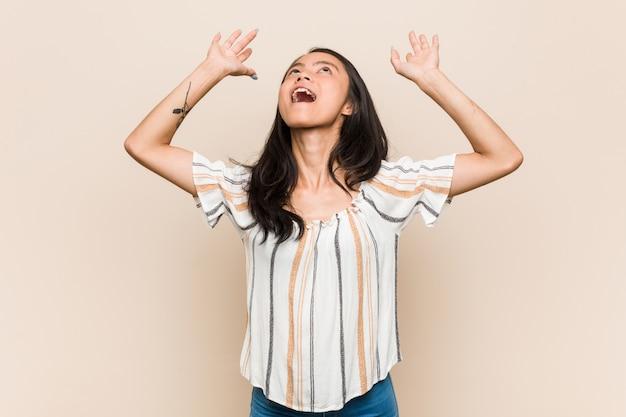 Jovem adolescente chinês bonito mulher loira jovem vestindo um casaco contra uma parede rosa gritando para o céu, olhando para cima, frustrado. Foto Premium