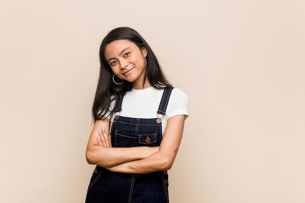Jovem adolescente chinês bonito mulher loira jovem vestindo um casaco contra uma parede rosa rindo e se divertindo. Foto Premium