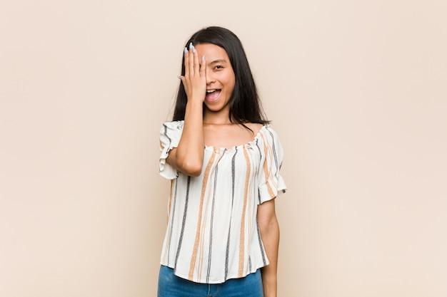Jovem adolescente chinês bonito mulher loira jovem vestindo um casaco contra uma parede rosa se divertindo cobrindo metade do rosto com a palma da mão. Foto Premium