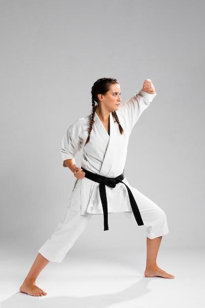 Jovem adulta com karatê de treinamento de lutador de faixa preta Foto gratuita
