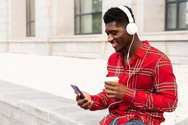 Jovem adulto do sexo masculino usando seu celular branco bebendo café Foto Premium
