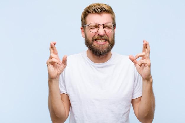 Jovem adulto loiro sorrindo e cruzando ansiosamente os dois dedos, sentindo-se preocupado e desejando ou esperando boa sorte Foto Premium