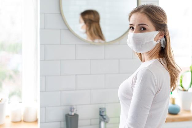 Jovem adulto usando uma máscara de proteção no banheiro Foto gratuita