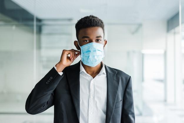 Jovem africano em máscara médica no rosto no escritório Foto gratuita