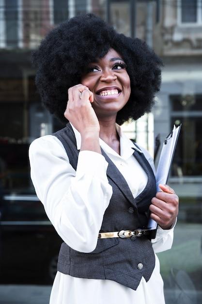 Jovem, africano, executiva, falando telefone móvel, segurando clipboard, em, mão Foto gratuita