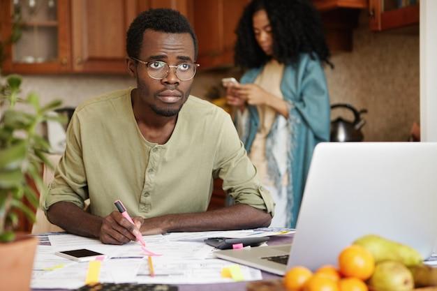 Jovem africano se sentindo estressado pagando contas online, calculando despesas com gás e eletricidade, sentado à mesa da cozinha em frente ao laptop aberto e fazendo anotações. estresse financeiro e dívidas Foto gratuita