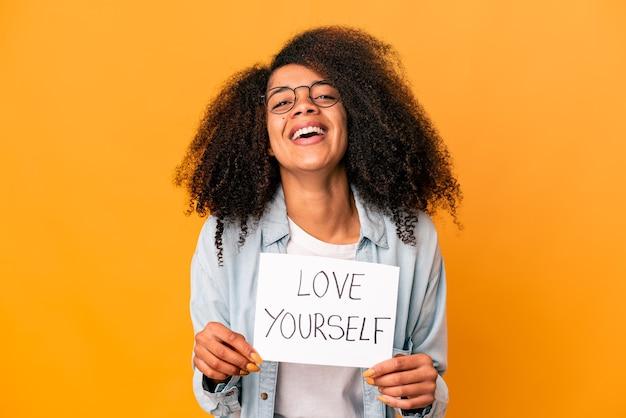 Jovem afro-americana encaracolada segurando um cartaz de amor a si mesmo Foto Premium