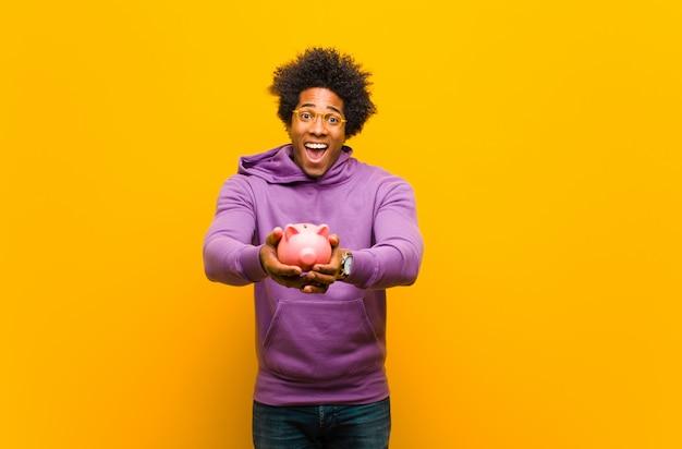 Jovem afro-americano com um cofrinho contra laranja volta Foto Premium