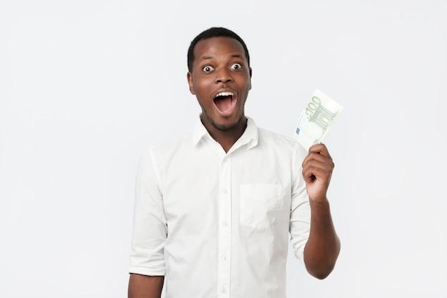 Jovem afro-americano com uma camisa segurando cem euros e surpreso Foto Premium