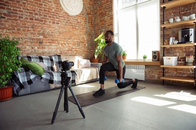 Jovem afro-americano, ensinando em casa cursos on-line de fitness, estilo de vida aeróbico e esportivo durante a quarentena, gravação na câmera, streaming Foto gratuita
