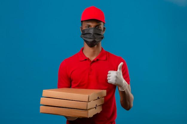 Jovem afro-americano entregador vestindo camisa polo vermelha e boné em máscara protetora e luvas de pé com pilha de caixas de pizza, mostrando os polegares sobre isolado azul Foto gratuita